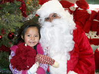 Native American child sitting on Santa's lap at Christmas