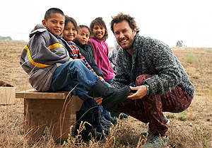 Founder Blake Mycoskie fits a Navajo youth for TOMS Shoes
